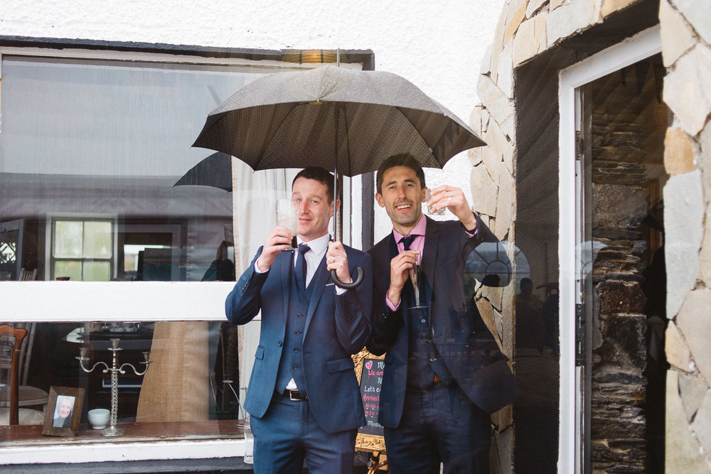 two wedding guests take shelter under umbrellas