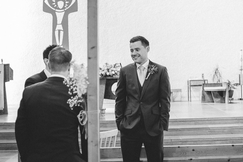 groom stands in chapel with his groomsmen