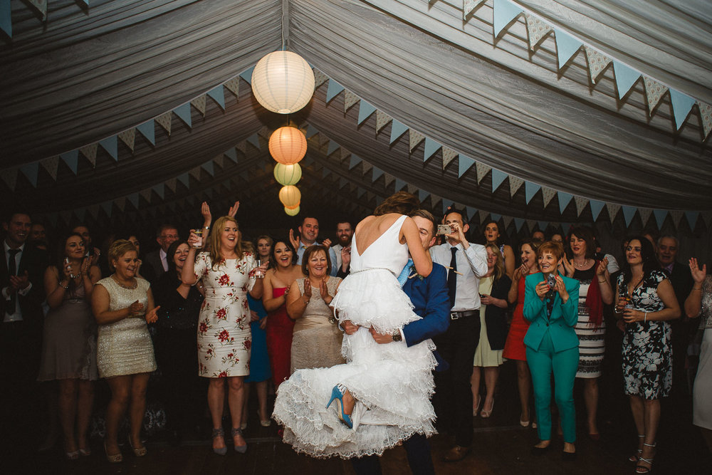 groom lifts bride to spin her on dance floor