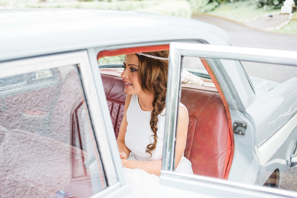 bride sits in wedding car