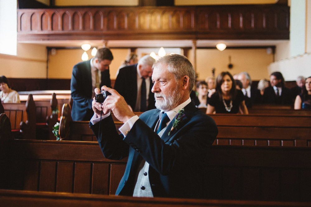 Grooms father takes a photograph