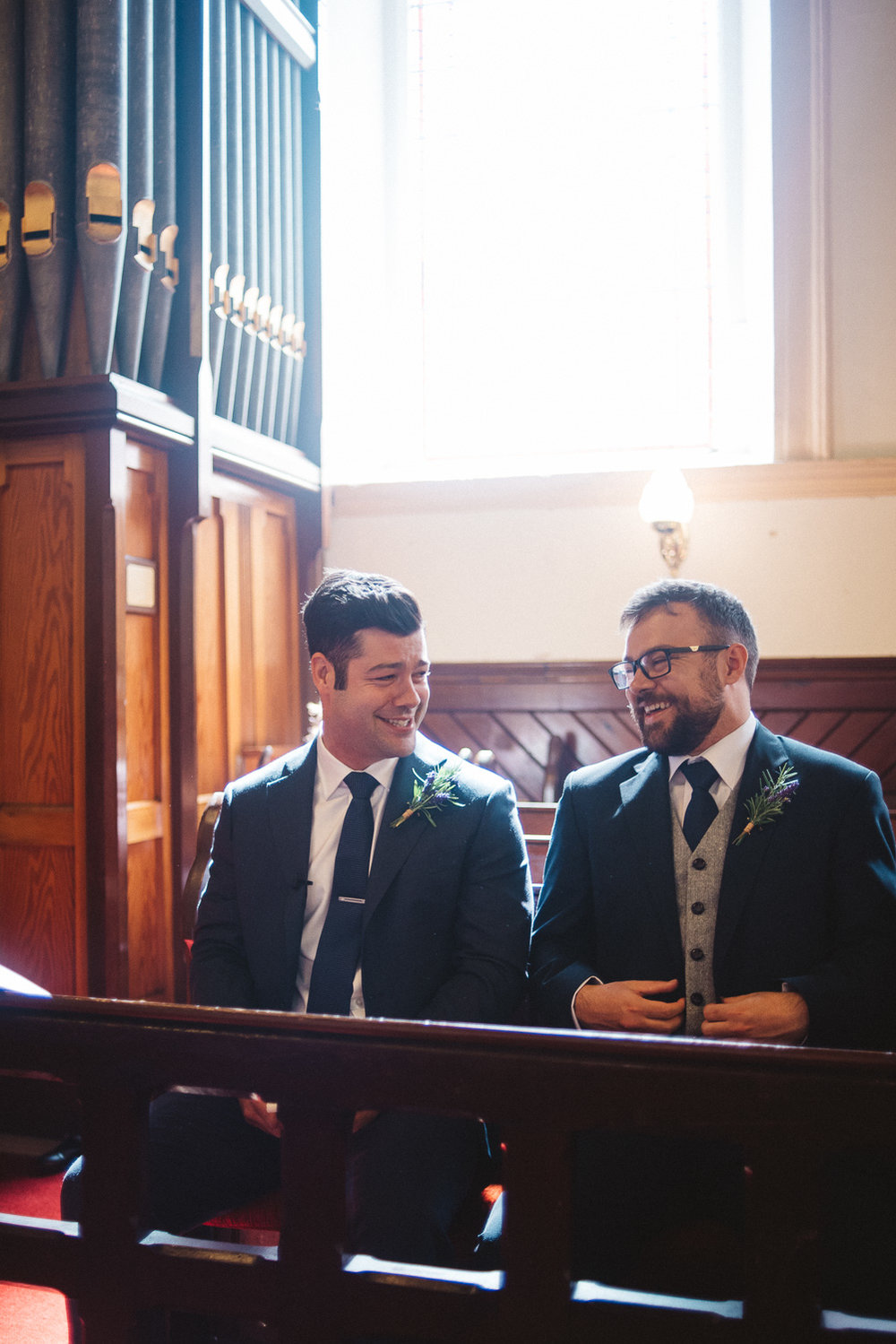 Groom in church laughing with his brother