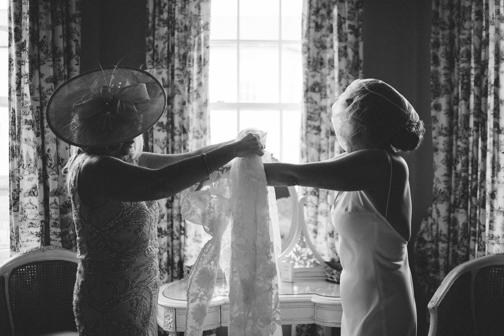 mother of bride helping bride into her dress