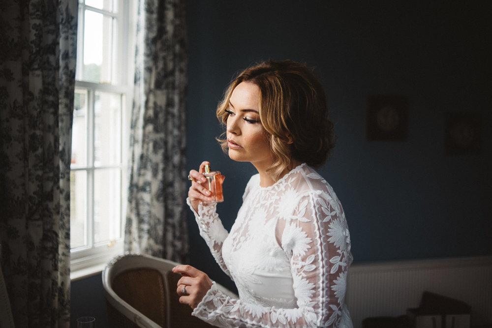 bride sprays perfume on herself