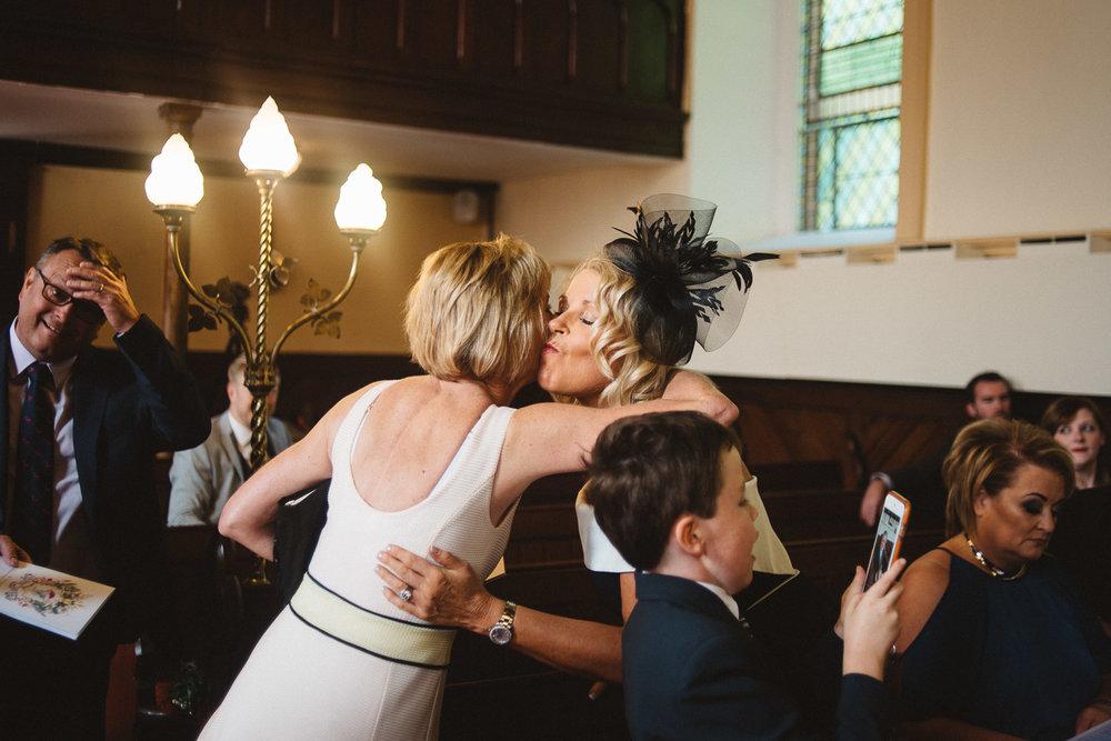 Wedding guests hugging.