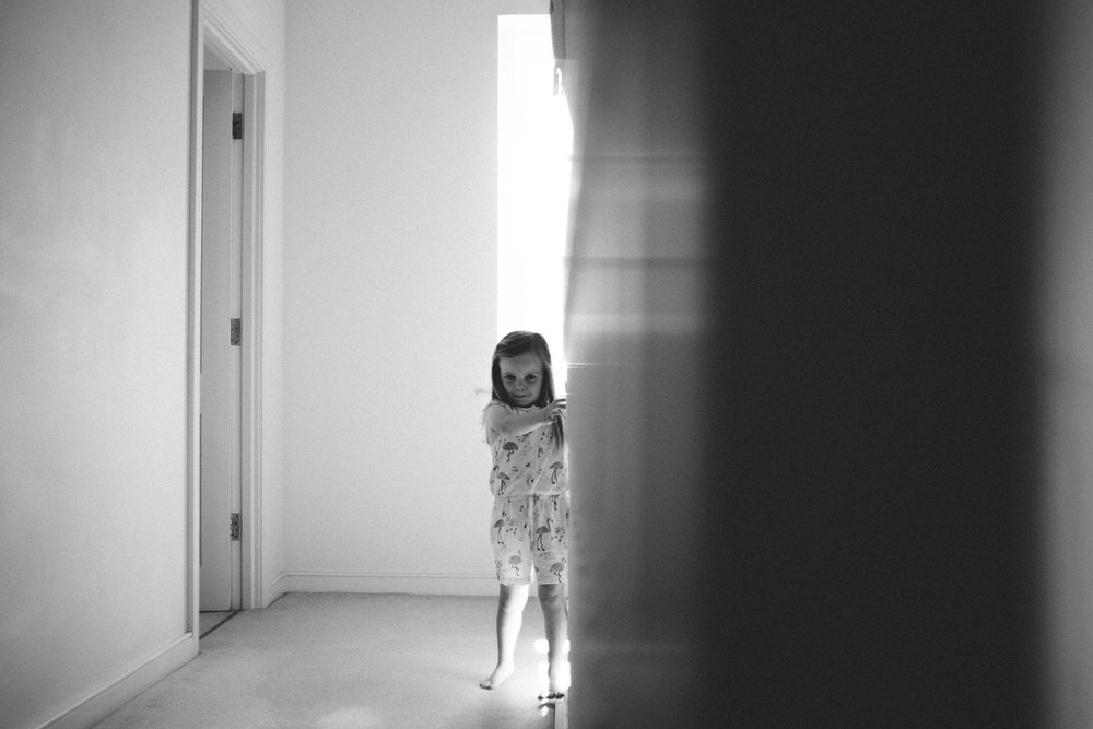 little girl peeking behind wall to the camera
