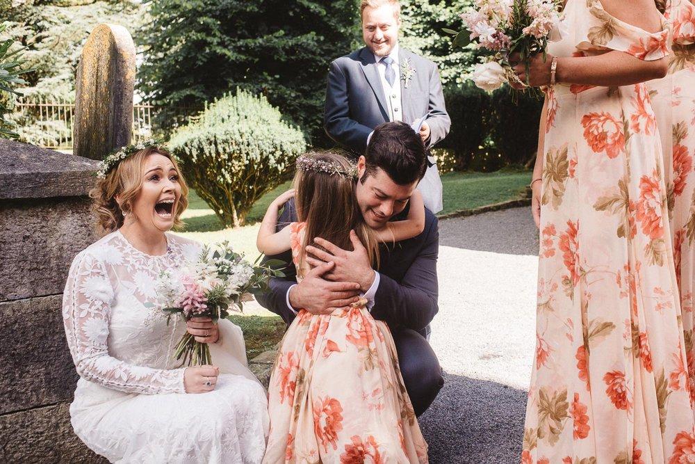 groom hugs little flower girl.