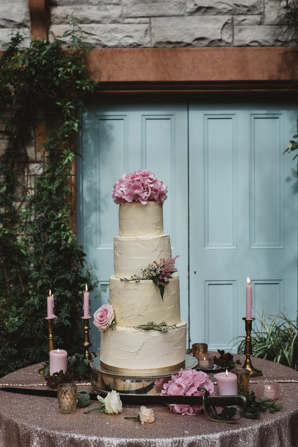 wedding cake with pink flowers and candles