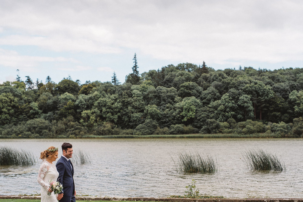 Bride and groom walk by the lake at Castle Leslie Wedding.