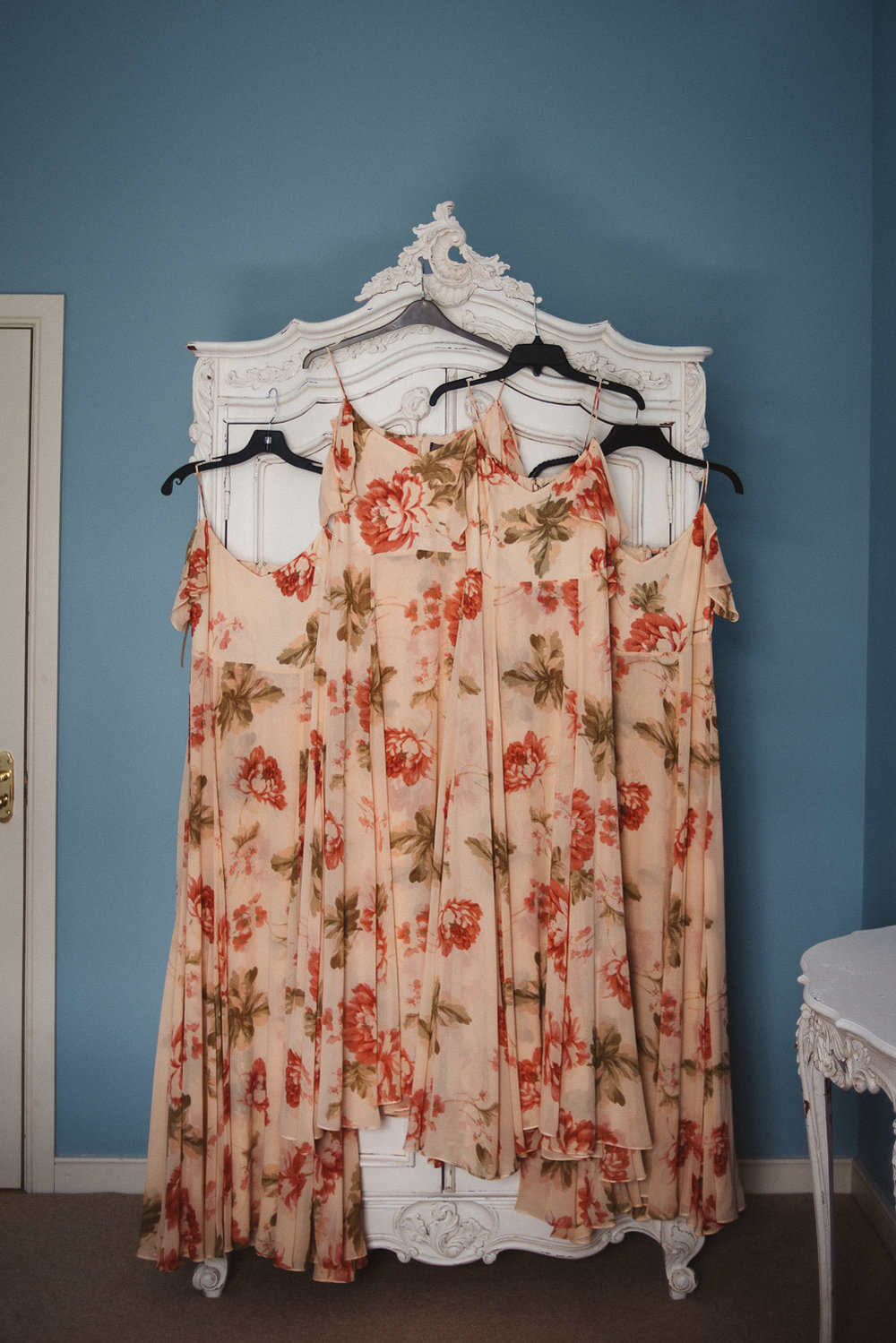 flower patterned bridesmaid dresses hanging on wardrobe
