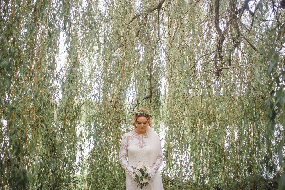 bride stands alone under a weeping willow tree