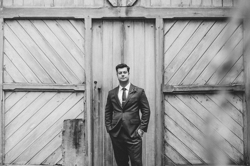 groom stands at wooden doors in wedding suit