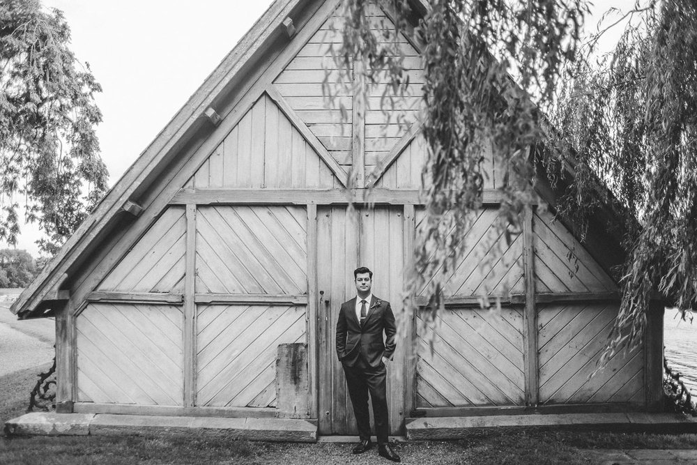 groom stands in front of boat house in wedding suit