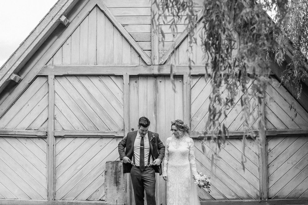 Bride and groom together in from of boat house
