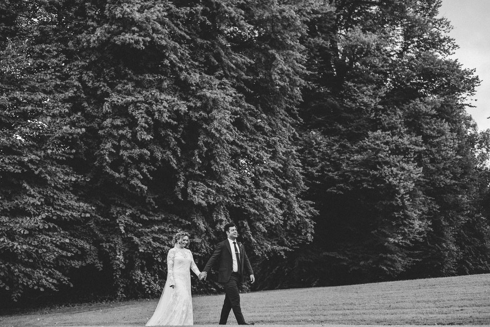 Bride and groom walk with a beautiful nature backdrop