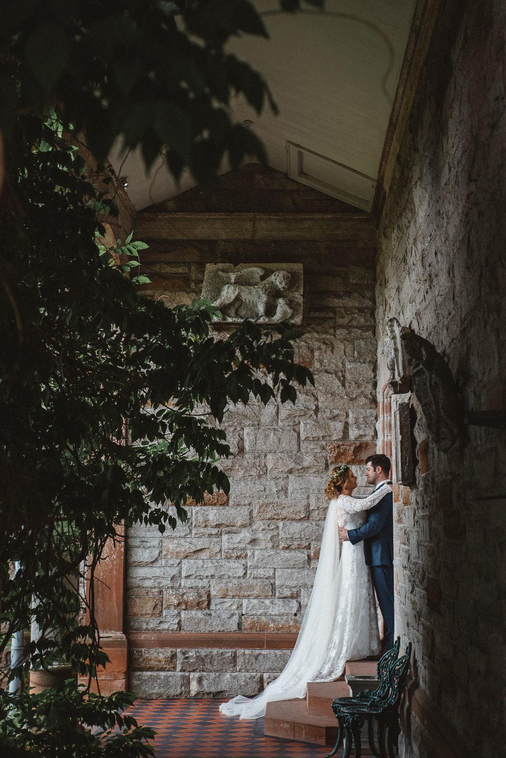Brode and groom stand in a pocket of light Castle Leslie Wedding.