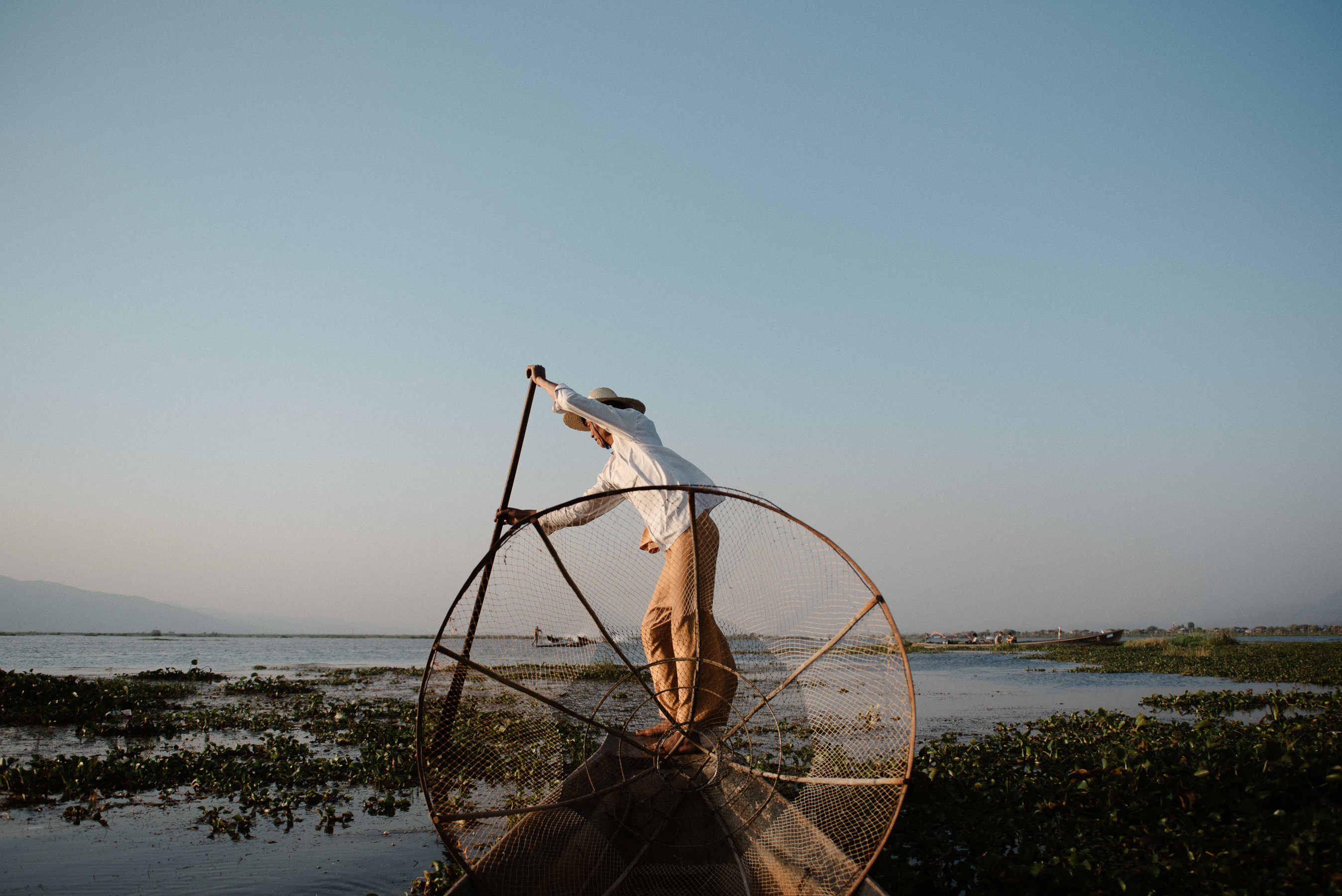 photo of a fisherman on a boat with his net in INle Lake, Myanmar
