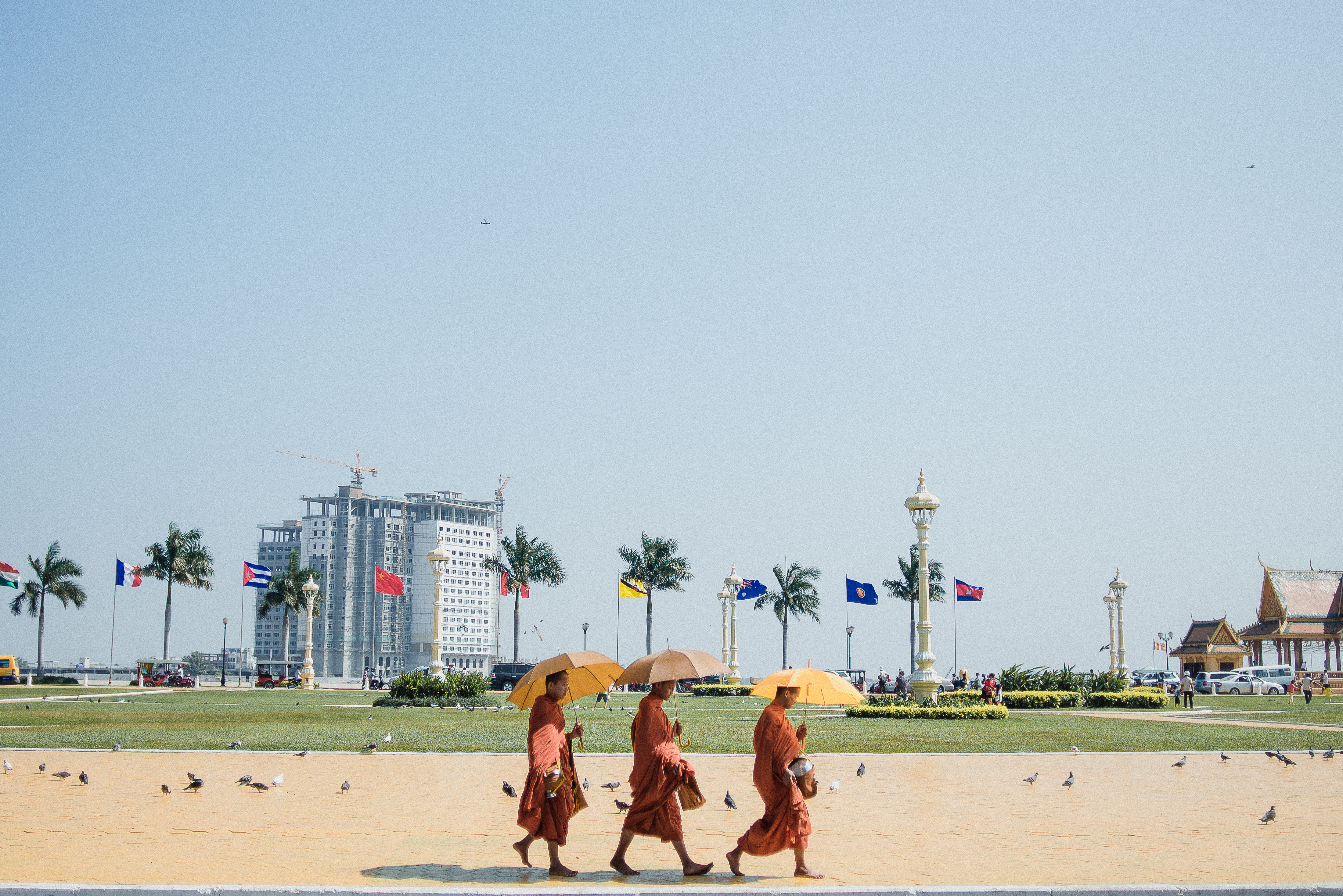 Photo of three monks walking with umbrellas in Cambodia