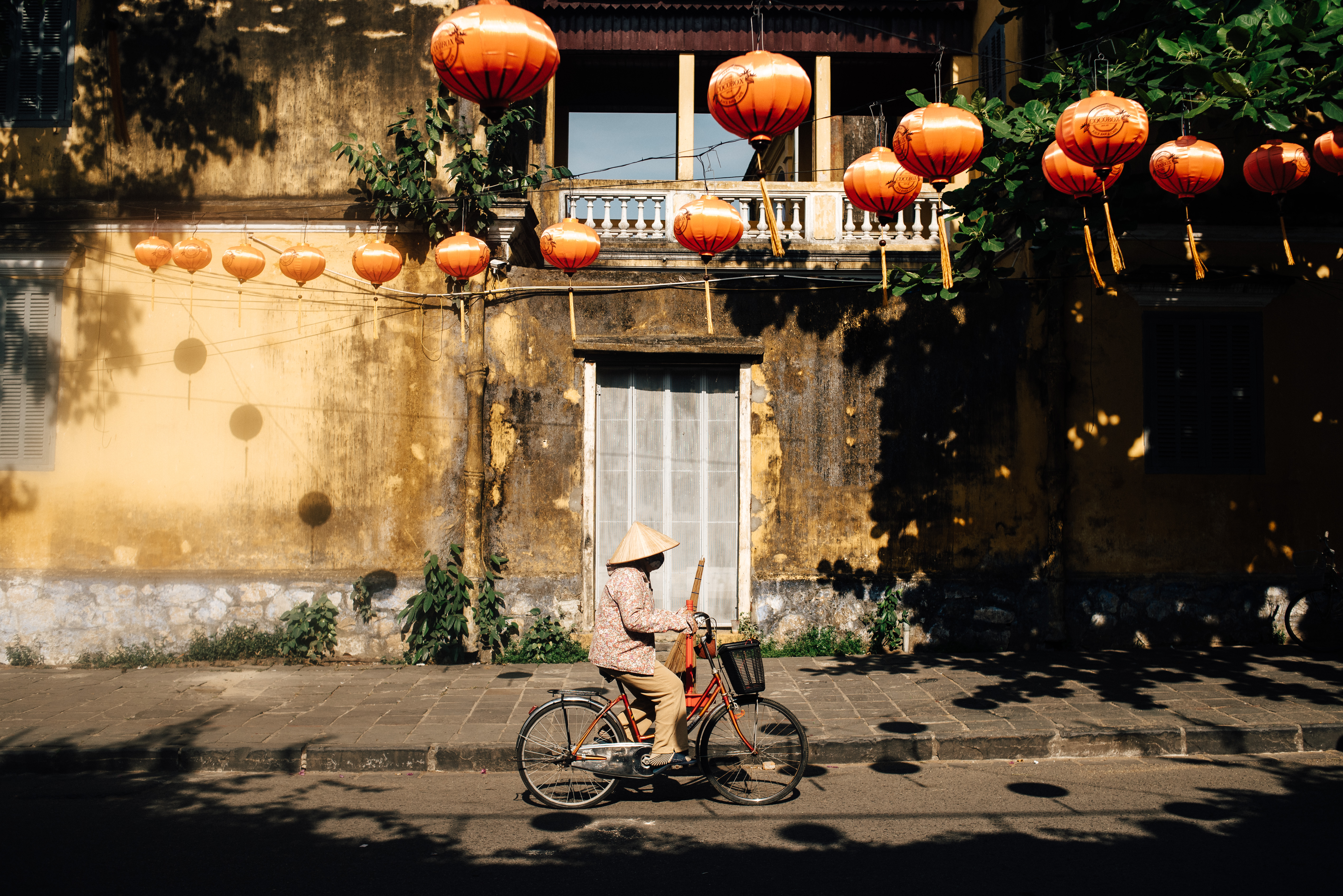 Photo of asian lady on bike with paper lanterns in Vietnam