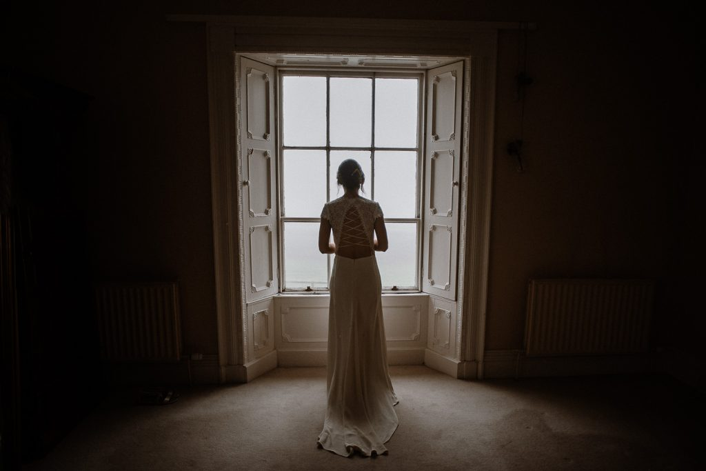full length of bride looking out the window in her wedding dress.