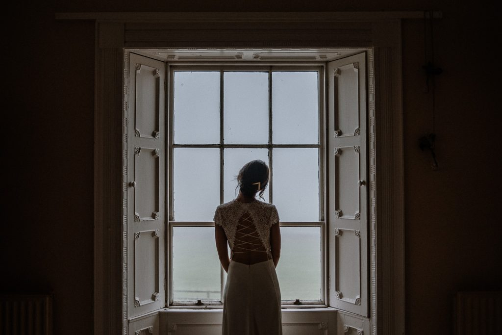 beautiful silhouette of bride at window