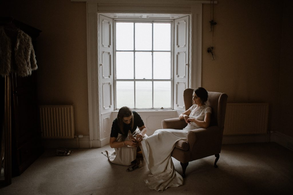bride sitting on chair while bridesmaid ties her shoes.