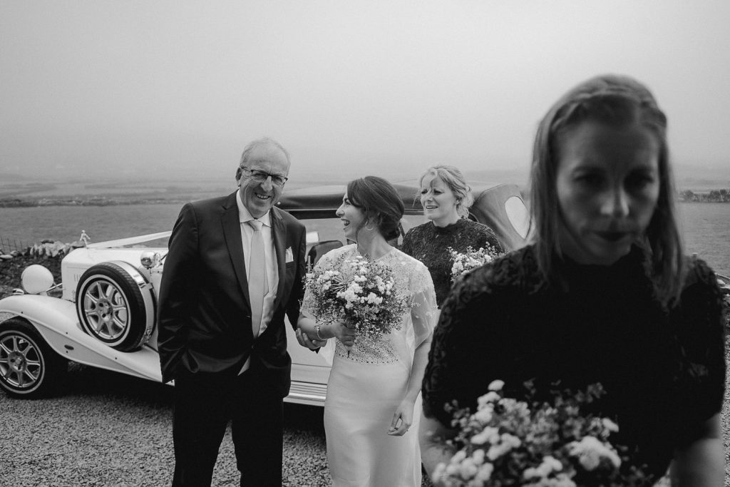 Bride with her father getting out of the car at chapel