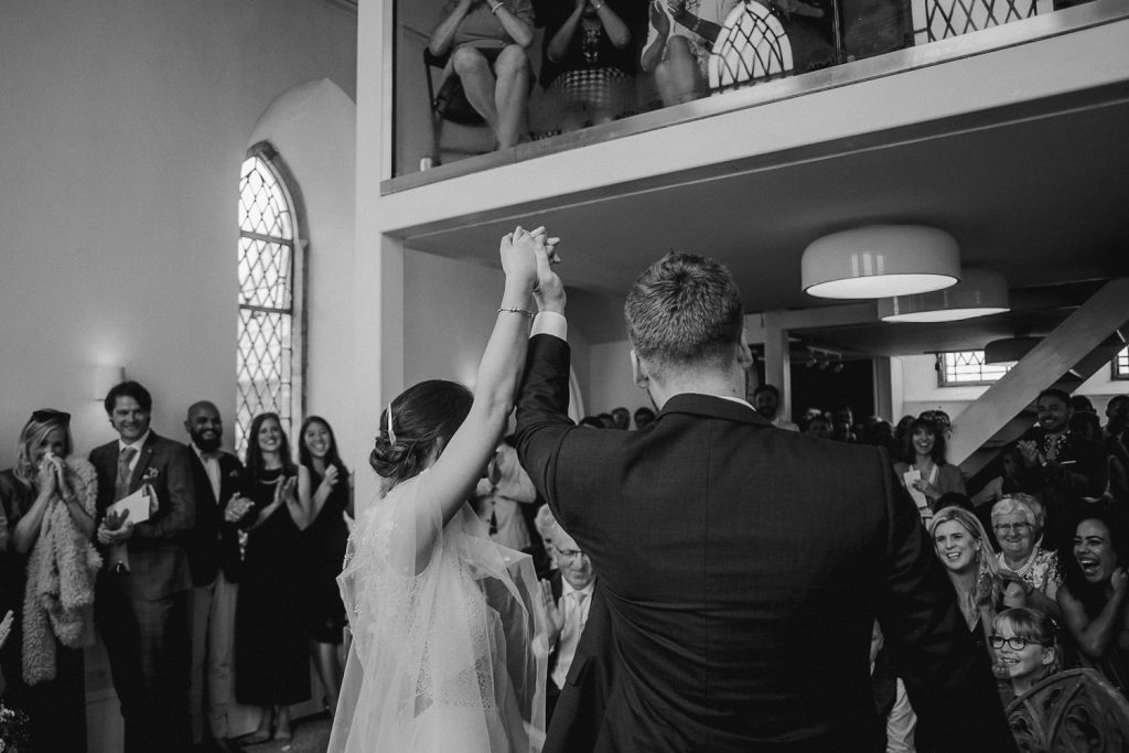 bride and groom raising hands in celebration of making vows