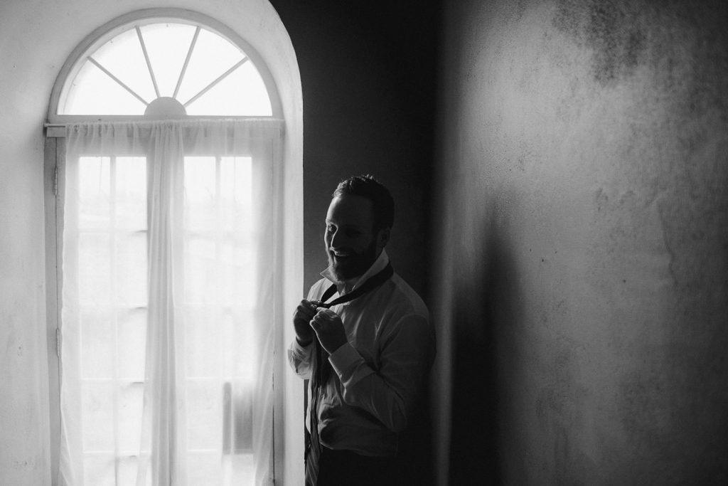 Happy groom doing tie by window light.