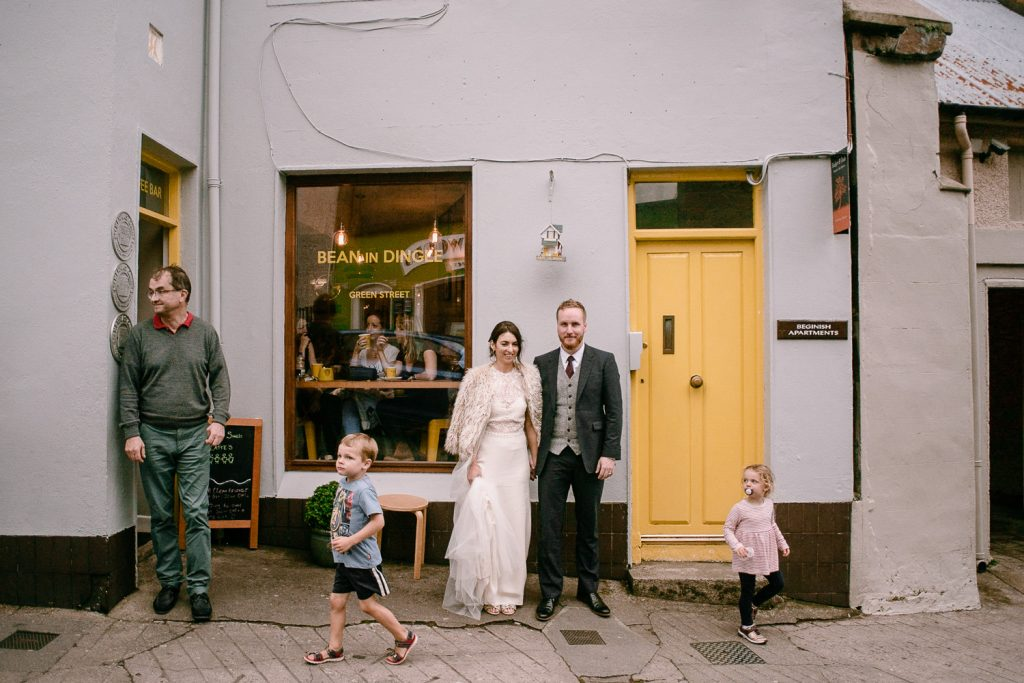 bride and groom in dingle town with kids running past