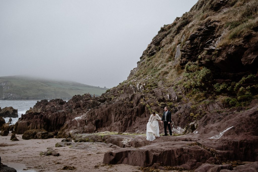 bride and groom walking on dingle beach