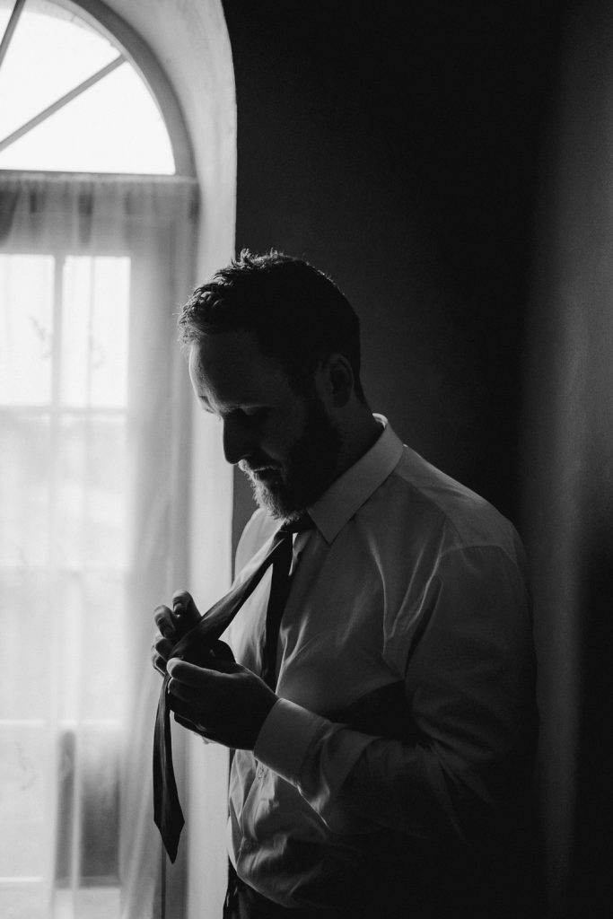 silhouette of groom doing his tie at window.