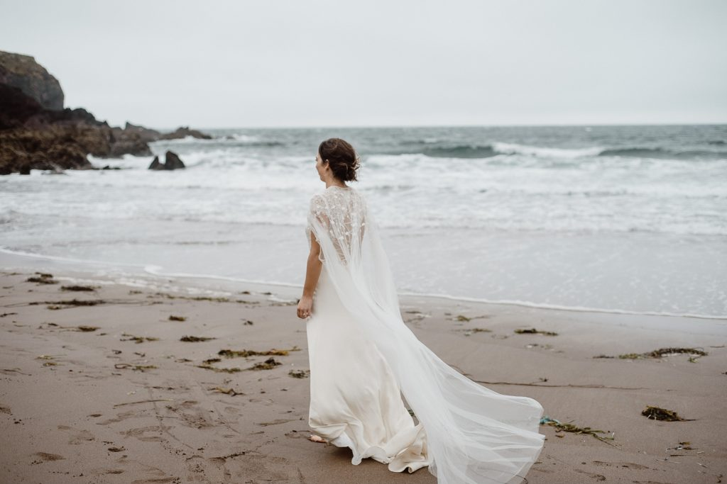 bride walking alone on beach with her cape and dress blowing in the wind