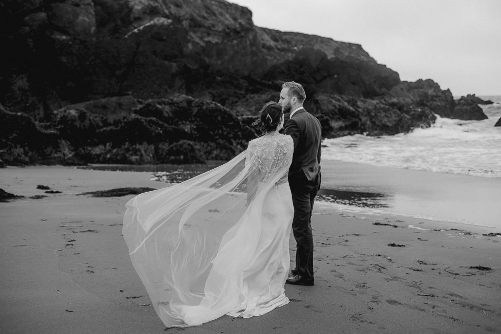 bride leading groom across beach and her dress is blowing in the wind