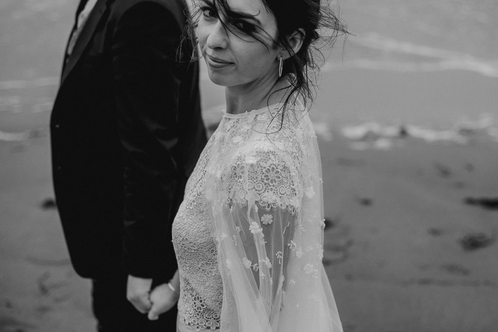 bride looking directly into camera as the wind blows her hair.