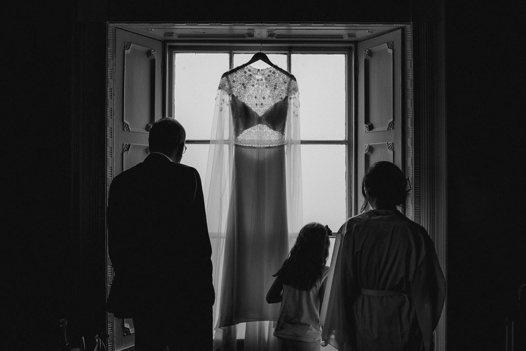 bride and father standing in front of wedding dress at window.