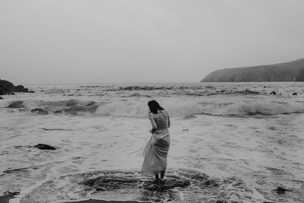 bride standing on rock as waves come in around her feet