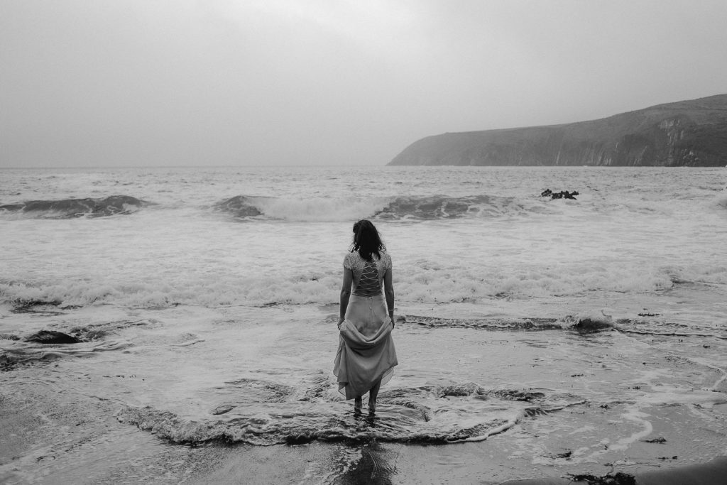 bride standing alone t the edge of the water as the waves crash around her feet