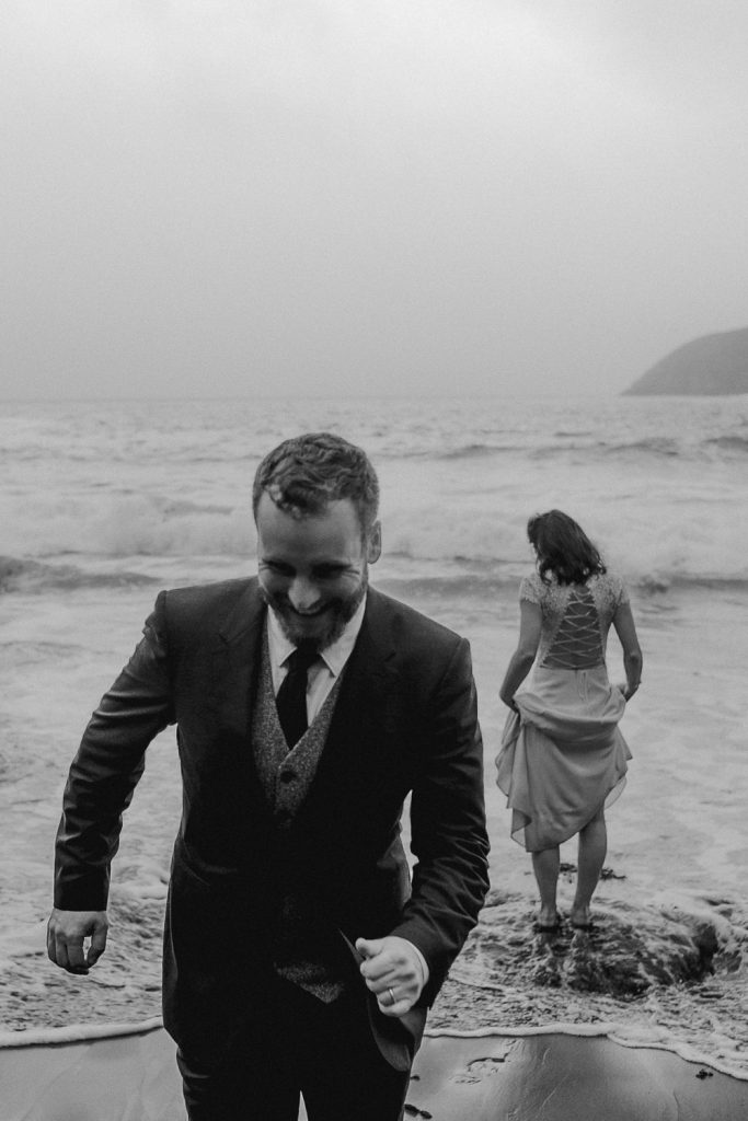 Groom running out of the sea as bride gets soaked