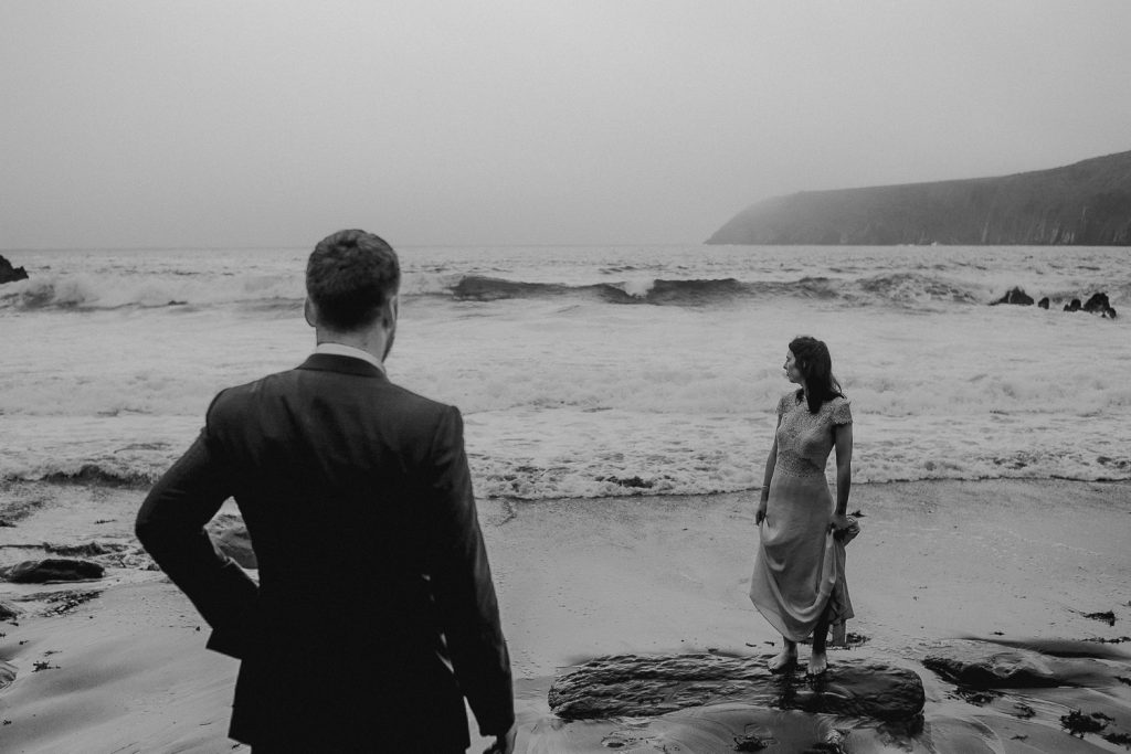 groom looks out at his bride on the beach