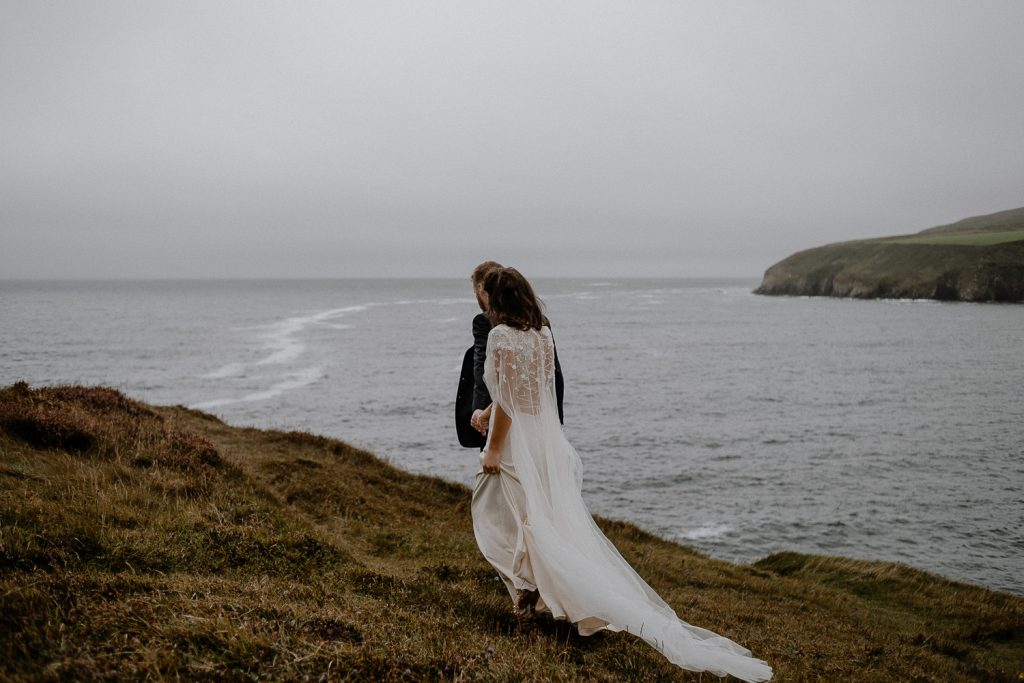 bride and groom walking towards cliff edge, sea in background