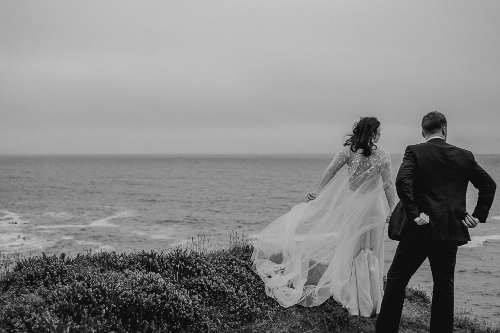 bride and groom on cliff edge, brides dress blowing in the wind. Dingle wedding photographer