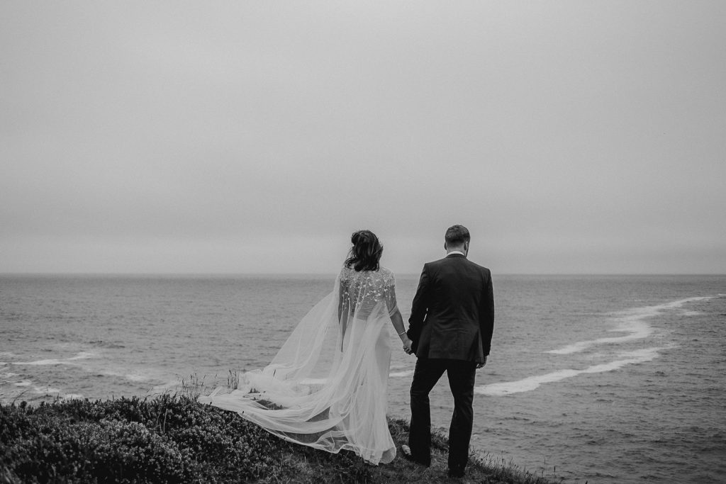 bride and groom on cliff edge looking out at sea