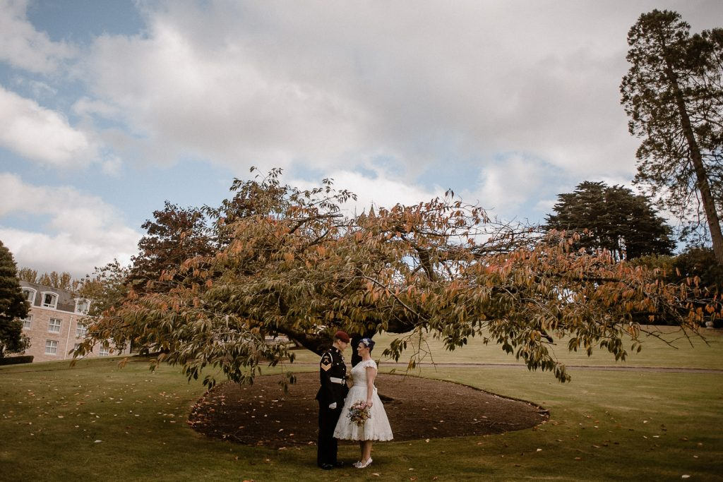 bride and groom standing in front of large tree in autumn