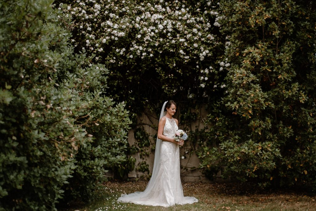 LIssanoure castle wedding. full length bridal portrait under while flowers and green trees