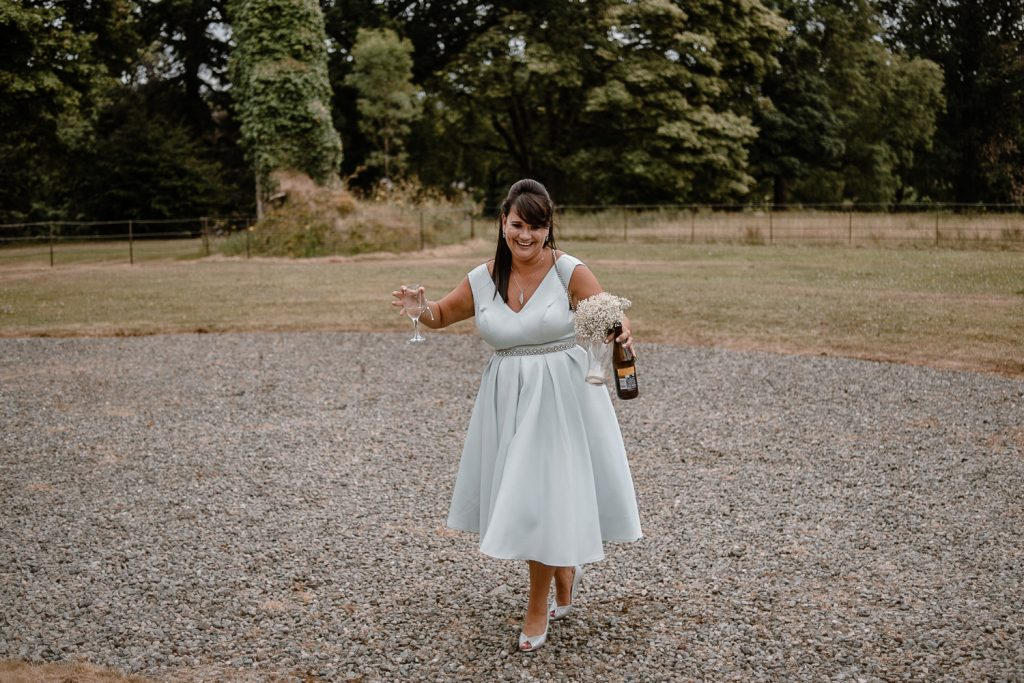 bridesmaid laughing with bottle and flowers in hand