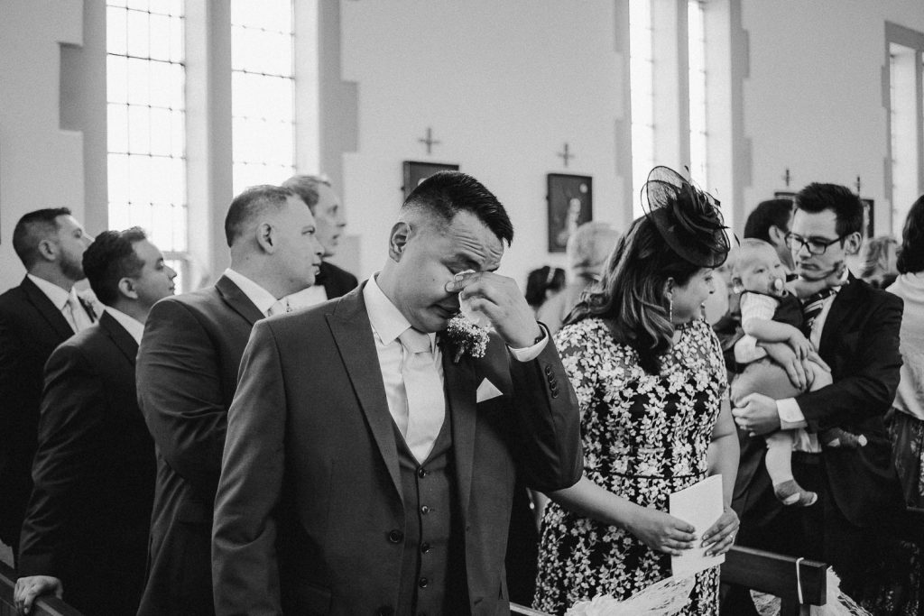 groom wiping tears away as he sees bride for the first time walking towards him