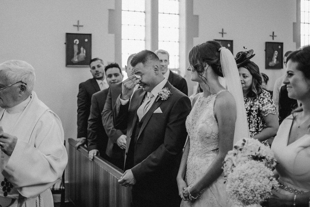 Groom wiping away tears as bride stands beside him