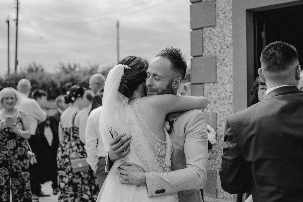 happy gust hugging bride