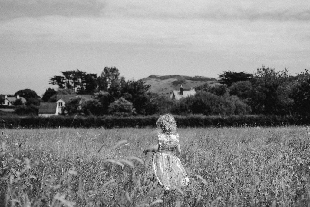 back of little girl walking in long grass